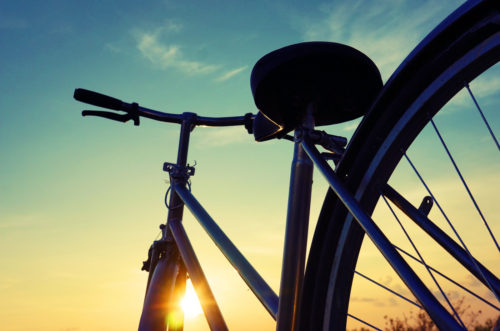 Beautiful close up scene of bicycle at sunset sun on blue sky with vintage colors silhouette of bike forward to sun wonderful rural of Mekong Delta Vietnam countryside